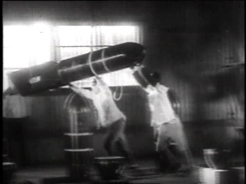 vidéos et rushes de workers guiding a missile suspended by rope / missiles lined up - missile