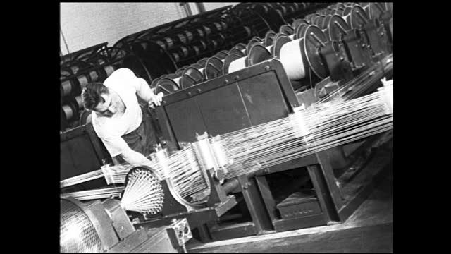 workers guiding cable into giant spools; woman typing off cable ends; construction site with trucks and large spools of cable scattered; man... - 1940 1949 bildbanksvideor och videomaterial från bakom kulisserna