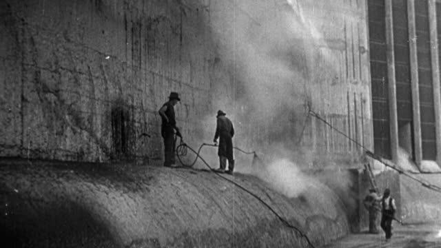 1949 montage workers hammering, spraying, and transporting rock while building a dam / united kingdom - dam stock videos and b-roll footage