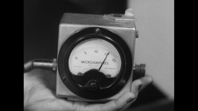 CU worker's hand holding microamphere meter with moving needle