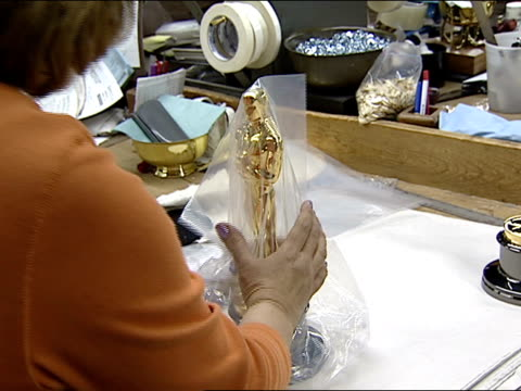 Workers handcraft Oscar Statuettes molded from goldplated britannium into an 8pound figurine at RS Owens Company factory on January 29 2003 in...