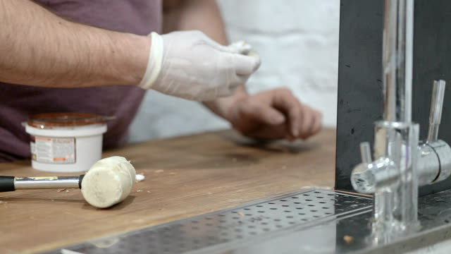 le mani del lavoratore puliscono la superficie del tavolo dopo il lavoro. - sigillante video stock e b–roll