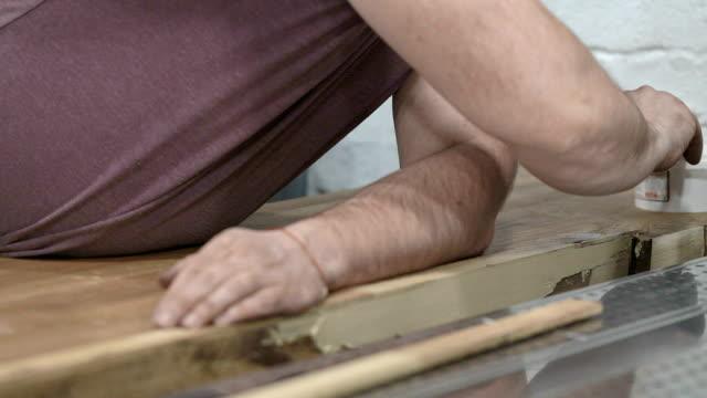 le mani dell'operaio coprono i dossi della superficie in legno del tavolo con sigillante. - sigillante video stock e b–roll