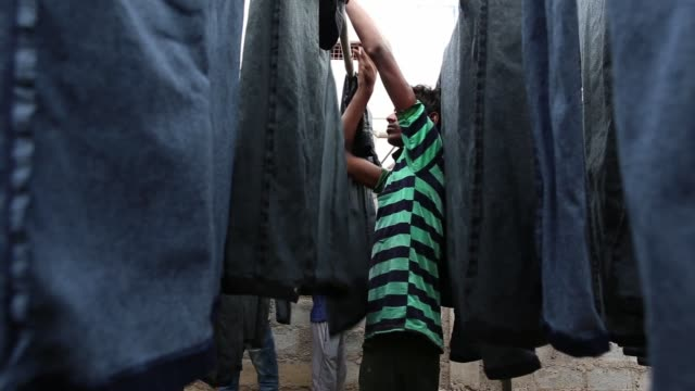 workers hang denim jeans outside the krishna jeans washers factory at an apparel park in the mundargi industrial area of ballari, karnataka, india,... - jeans stock videos & royalty-free footage