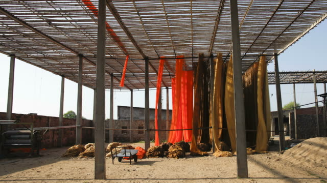vídeos de stock, filmes e b-roll de workers hang newly dyed fabric up to dry at a sari garment factory in rajasthan, india. - tintura