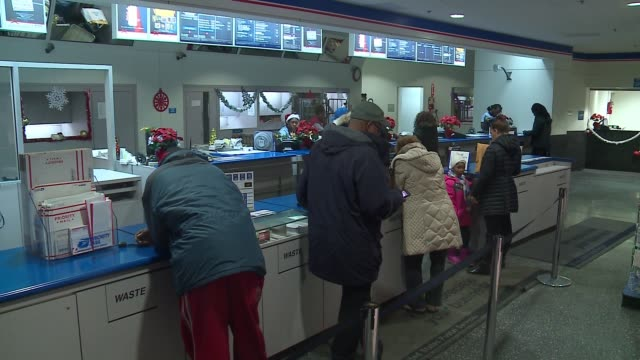 workers help customers at counter with packages during holiday season in chicago on dec. 21, 2016. - post office stock videos & royalty-free footage
