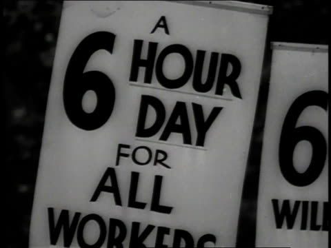 Workers holding picket signs reading 'A 6 Hour Day for All Workers' 'The Hours of Labor are Too Long' and 'We Manufacture Electric Wire and Cable' /...