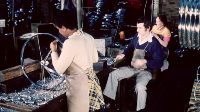 1974 montage workers in a factory assembling bicycle wheels and applying tires to bike rims / nottingham, england, united kingdom - archival stock videos & royalty-free footage
