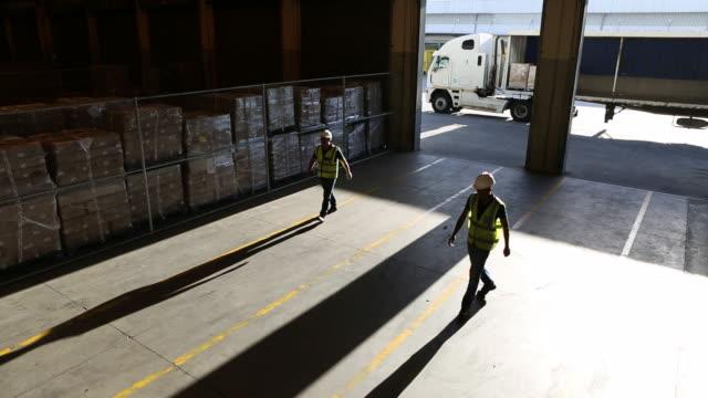 vídeos y material grabado en eventos de stock de workers in a large food distribution warehouse - paleta herramientas industriales