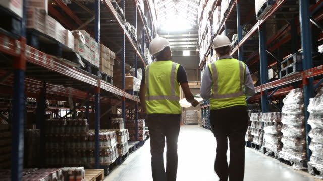 workers in a large food distribution warehouse - trousers stock videos & royalty-free footage