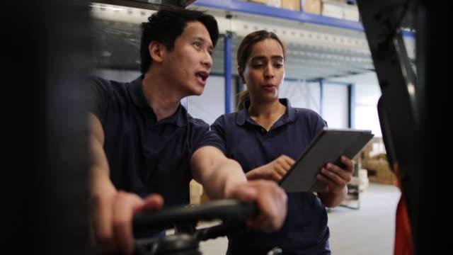 vídeos de stock, filmes e b-roll de workers in a warehouse discussing order preparation - cilindro veículo terrestre comercial