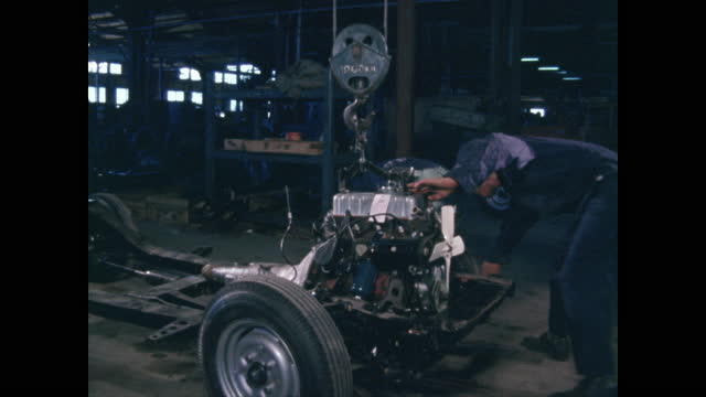 workers in automotive manufacturing install motor to chassis - taipei stock videos & royalty-free footage