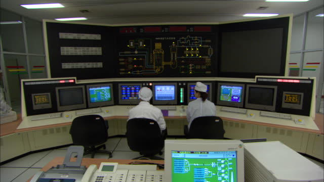 vídeos de stock e filmes b-roll de ws workers in control room at tsinghua university's nuclear pebble bed reactor, beijing, china - central de energia nuclear