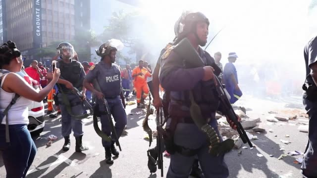 vídeos de stock e filmes b-roll de workers in durban protest over anc misrule armed police try to keep control and gunfire can be heard - eleição