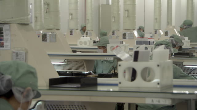 ms selective focus workers in factory uniforms working at various stations at suntech solar factory, wuxi, jiangsu, china - protective workwear stock-videos und b-roll-filmmaterial