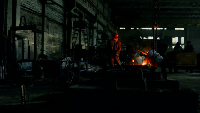 workers in foundry. pouring excess molten metal - melting stock videos & royalty-free footage