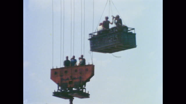 1978 Workers in hardhats hoisted into the air on a sunny day