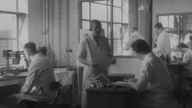 1941 montage workers in laboratories preparing treatments for diphtheria / united kingdom - diphtherie stock-videos und b-roll-filmmaterial