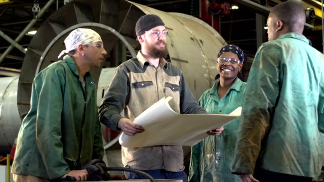 workers in metal fabrication shop, looking at plans - four objects stock videos & royalty-free footage