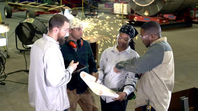 operai in officina di fabbricazione di metalli, piani, saldatore - stare in piedi video stock e b–roll