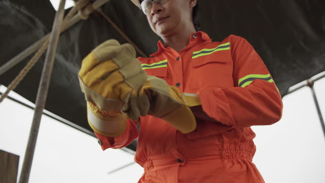 workers in production plant  looking at the camera as he puts on work gloves. - reflective clothing stock videos & royalty-free footage