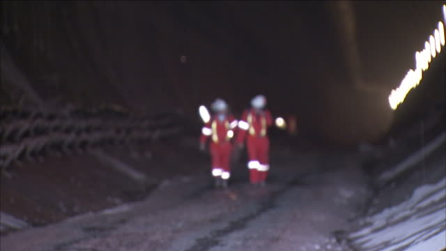 workers in safety equipment walk out of a tunnel. - safety equipment stock videos & royalty-free footage