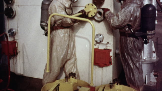 1957 montage workers in safety gear attempting to attach the wrong pump to a nuclear reactor and finding it doesn't fit / united kingdom - nuclear power station stock videos and b-roll footage