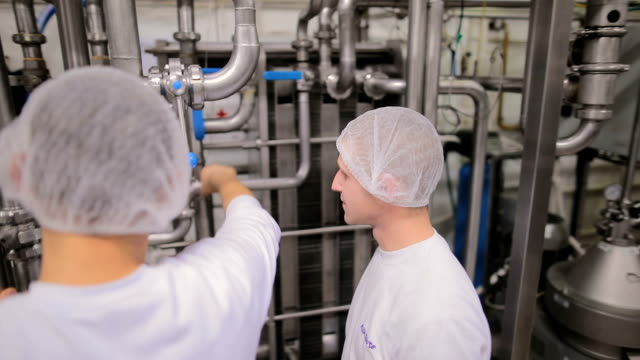 workers in the food factory on the control station.friendship,education - dairy factory stock videos & royalty-free footage