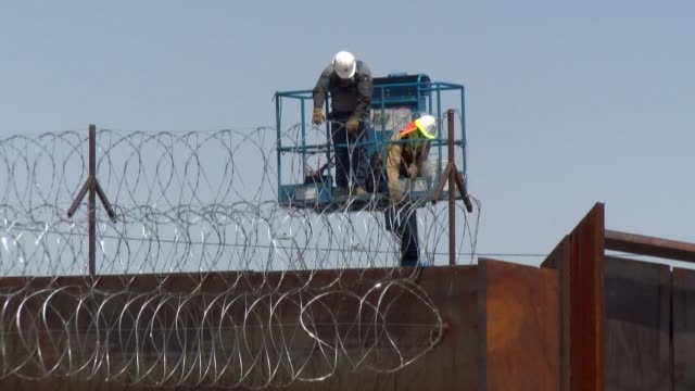 workers in the service of the the united states government place barbed wire on the fence that runs along the border with mexico near the crossing... - fence stock videos & royalty-free footage