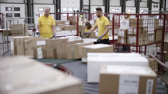 ld workers in warehouse taking packages off the conveyor belt - belt stock videos and b-roll footage