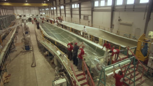 ha ws workers in wind turbine factory surrounding turbine part wrapped in plastic/ pipestone, minnesota - power equipment stock videos & royalty-free footage