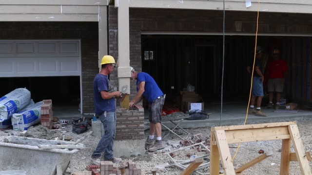 workers including bricklayers insulation installers spraying foam construction materials at a construction site for single family townhomes in... - isoliermaterial stock-videos und b-roll-filmmaterial