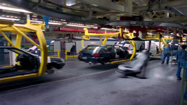 stockvideo's en b-roll-footage met t/l, ms, workers inserting car seats at car assembly line, dagenham, england - assemblagelijn