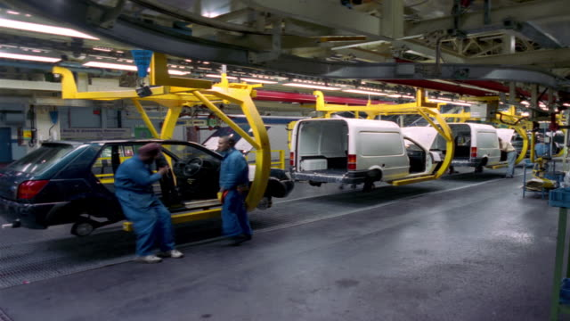 t/l, ms, workers inserting car seats at car assembly line, dagenham, england - car plant stock videos & royalty-free footage
