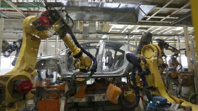 Workers inspect components for vehicles on the production line at a plant operated by Dongfeng PeugeotCitroen Automobile Ltd the joint venture...