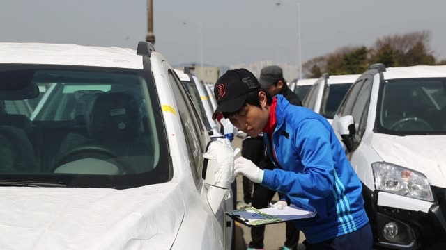 stockvideo's en b-roll-footage met workers inspect parked general motors co chevrolet automobiles bound for export at the port of incheon in incheon south korea export images at... - incheon