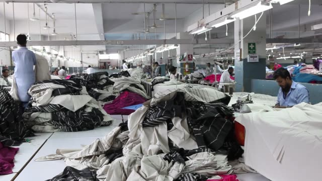 vidéos et rushes de workers inspect pieces of fabric ahead of stitching at dl nash ltd a textile manufacturer in karachi pakistan on saturday sept 10 workers use sewing... - usine textile