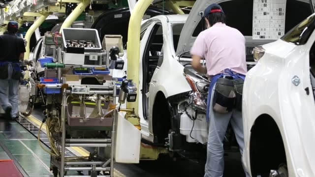 stockvideo's en b-roll-footage met workers install a bumper on the prius hybrid and prius plugin hybrid vehicle production line of the toyota motor corp tsutsumi plant in toyota city... - toyota motor