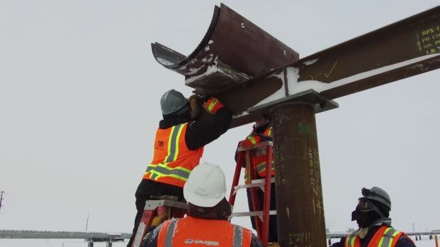 workers install a support for a new pipeline being built to replace an aging line outside a bp plc production facility in prudhoe bay, alaska, u.s.,... - plc stock videos & royalty-free footage