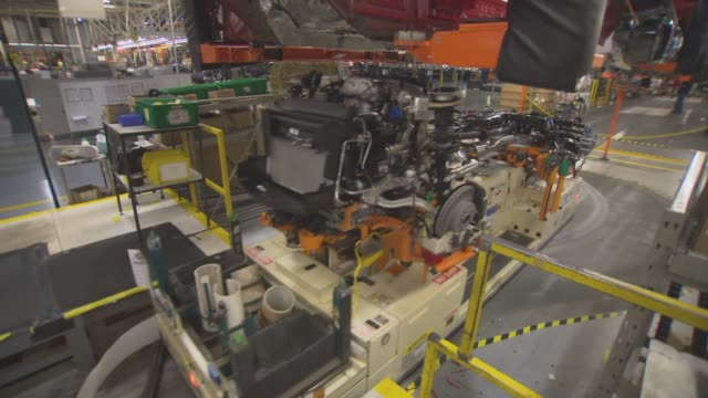 vídeos de stock e filmes b-roll de workers install engine and axle frames on cadillac vehicles at the general motors design center factory floor in warren michigan on november 20th... - general motors