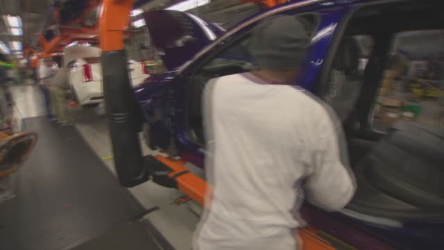 workers install front and reseats to cadillac vehicles at the general motors design center factory floor in warren michigan on november 20th 2013 - general motors stock videos & royalty-free footage