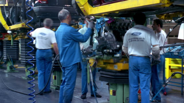 t/l, ms, workers installing engines at car assembly line, dagenham, england - inghilterra video stock e b–roll