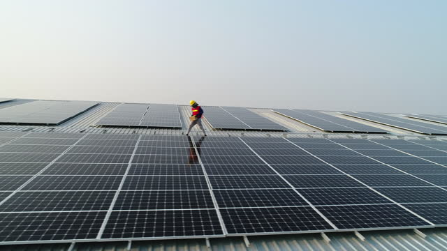 arbeiter installieren solarmodule auf dem werksdach - dach stock-videos und b-roll-filmmaterial