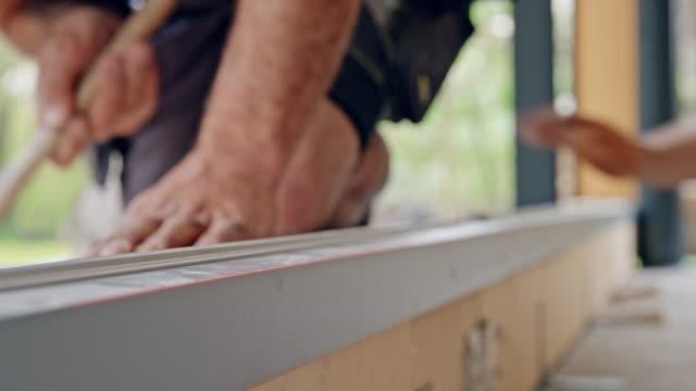 stockvideo's en b-roll-footage met r/f werknemers het grote glazen deurframe installeren - installeren