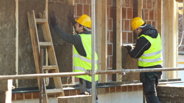 workers insulating a newly built house - insulator stock videos & royalty-free footage