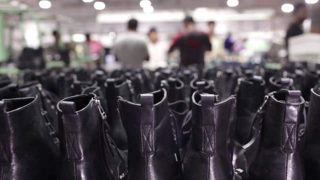 Workers labor behind a row of shoes on an assembly line at a Virola Shoes Pvt manufacturing facility in Agra Uttar Pradesh India on Friday June 23...
