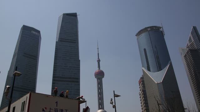 workers labor in front of the oriental pearl radio & tv tower at a construction site in the lujiazui district of shanghai, china, on thursday, april... - lujiazui stock videos & royalty-free footage