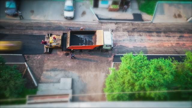 vídeos de stock, filmes e b-roll de workers laid asphalt in the residential sector. time lapse. - pista asfaltada