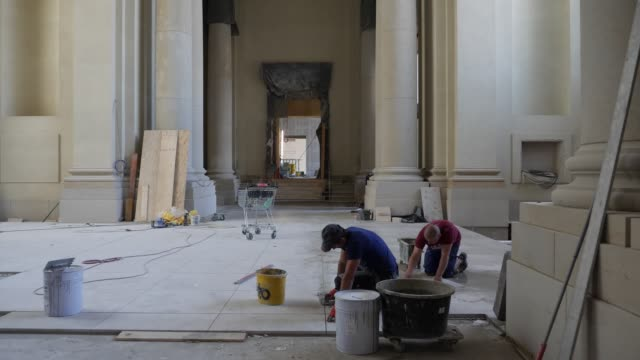 workers lay tiles in the central entrance hall of the humboldt forum on june 17 2019 in berlin germany the humboldt forum will occupy the rebuilt... - berliner stadtschloss stock-videos und b-roll-filmmaterial