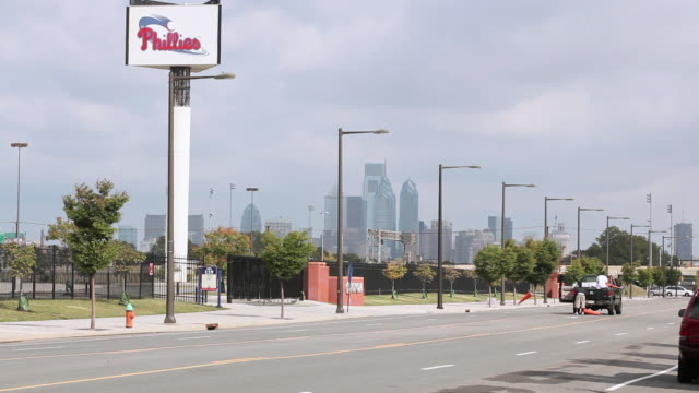 ws workers laying cones on street outside citizens bank park in front of city skyline / philadelphia, pennsylvania, united states - philadelphia phillies stock-videos und b-roll-filmmaterial